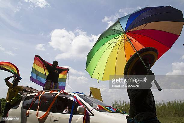 A person holds an umbrella bearing the colors of the rainbow flag as others wave flags during the the first gay pride rally since the overturning of...