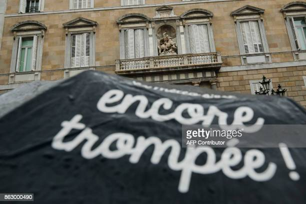 A person holds an umbrella with a text reading in French 'Tricked again' outside the Generalitat Palace in Barcelona on October 19 2017 Spain said...