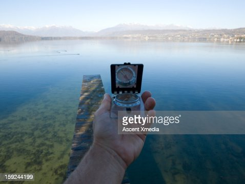 Person holds compass along wooden dock, lake : Stock Photo