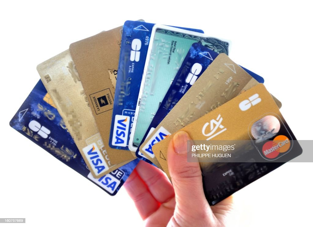 A person holds credit cards on February 5, 2013 in Lille. French police has arrested, early this morning in Paris and in several French and overseas departments, 22 people in connection with the trade of credit cards numbers on internet. AFP PHOTO PHILIPPE HUGUEN