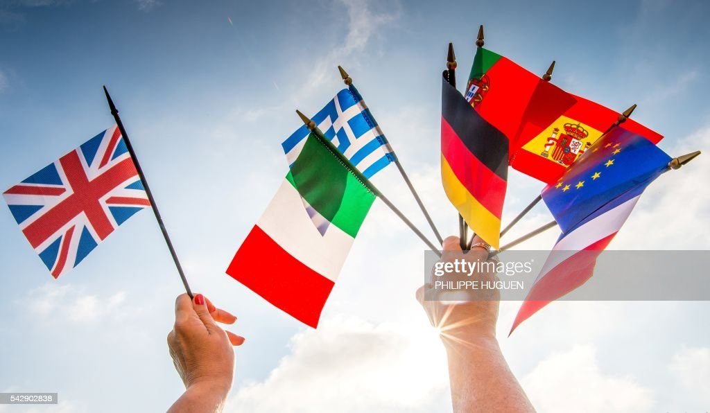 A person holds European country flags in an hand and a United Kingdom flag in another on June 25, 2016 in Lille, northern France. European Commission chief Jean-Claude Juncker said Britain's planned departure from the European Union was 'not an amicable divorce' but called for it to be quick. 'I do not understand why the British government needs until October to decide whether to send the divorce letter to Brussels,' he told German public broadcaster ARD late June 24, 2016. HUGUEN