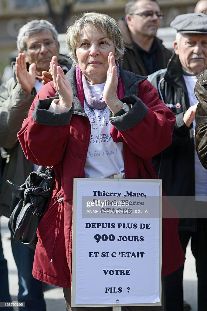 A person holds on March 16, 2013 a placard, reading: 'Thierry, Marc, Daniel, Pierre hostages in Mali for 900 days -- we do not forget you,' during a gathering in the southern French city of Marseille to show their support for the four French hostages kidnapped by Al-Qaeda in the Islamic Maghreb (AQMI) on September 16, 2010 in Niger and held in Mali.