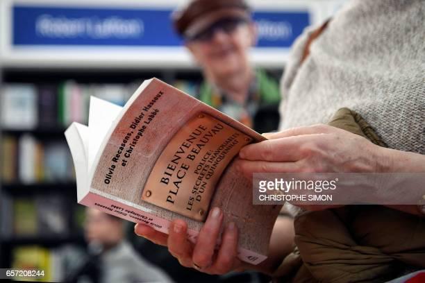 A person holds the book 'Bievenue place Beauvau Police le secrets inavouables d'un quinquennat' on March 24 2017 during the International Book Fair...