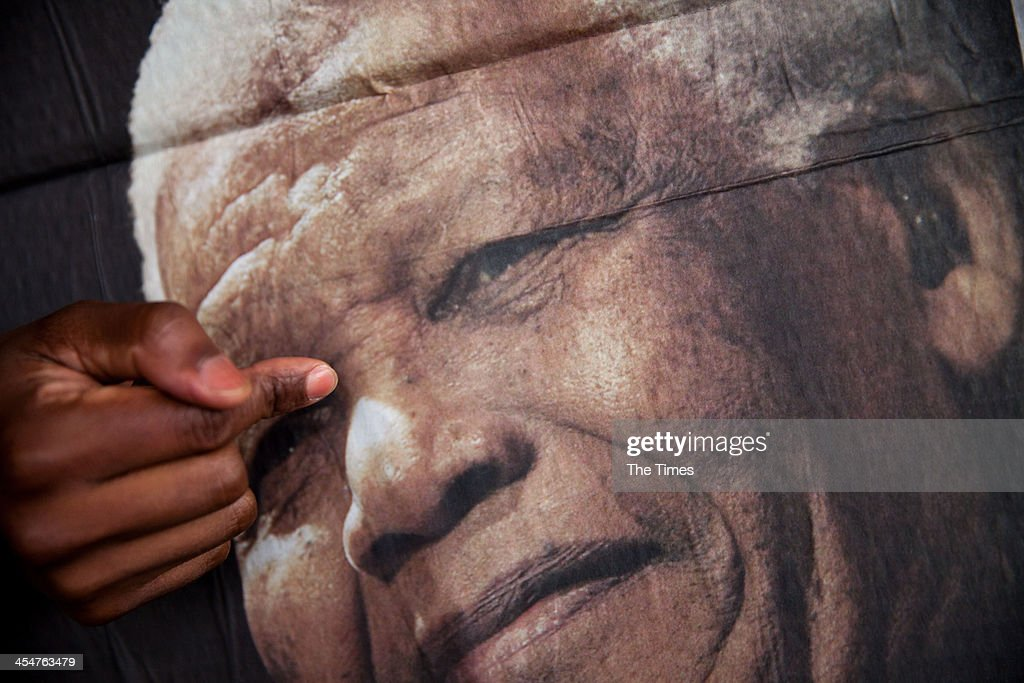 A person holds up a placard showing Nelson Mandelas face during his memorial service at the FNB stadium for the memorial service of former president Nelson Mandela on December 10, 2013 in Johannesburg, South Africa.