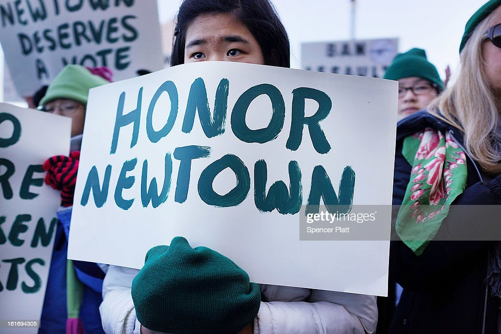 A person holds up a sign during a rally at the Connecticut State Capital to promote gun control legislation in the wake of the December 14, 2012, school shooting in Newtown on February 14, 2013 in Hartford, Connecticut. Referred to as the 'March for Change' and held on the two-month anniversary of the massacre in Newtown, Connecticut, participants called for improved gun safety laws. Among the safety measures being demanded are for universal background checks, more work within the mental health community and restricting high-capacity magazines.