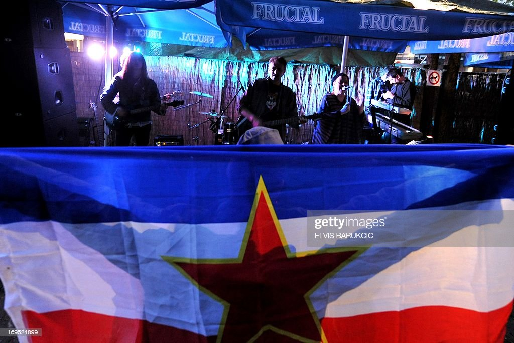 A person holds up a Socialist Federative Republic of Yugoslavia flag at a gathering to comemorate ex-Yugoslav communist leader Josip Broz Tito's birthday in Sarajevo, on May 25, 2013. As the last Yugoslav king Petar II Karadjordjevic was reburied in Serbia on May 26, hundreds of supporters of his post-World War II political rival, communist leader Josip Broz Tito, marked the 121st anniversary of his birthday throughout his former homeland. Josip Broz was born on May 25, 1892 in Croatia. He later became Yugoslav communist party leader and a lifetime president of Yugoslavia. He died on May 4, 1980 and after his death Yugoslavia fell apart and the socialist ideas mostly vanished in the region torn apart by nationalist policies led by his successors in all ex-Yugoslav republics. AFP PHOTO / ELVIS BARUKCIC