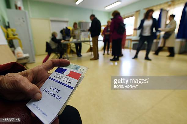 A person holds up an electoral card at a polling station during the first round of the French departementales elections on March 22 2015 in...