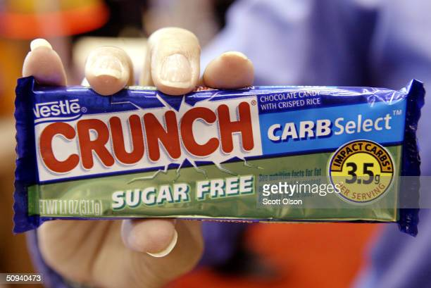 A person holds up the new Nestle Crunch Carb Select Sugar Free candy bar at the All Candy Expo trade show June 8 2004 in Chicago Illinois According...