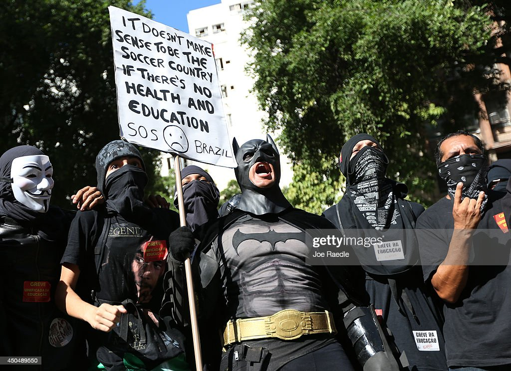A person in a Batman costume holds a sign during a World Cup demonstration on June 12, 2014 in Rio de Janeiro, Brazil. This is the first day of World Cup play.
