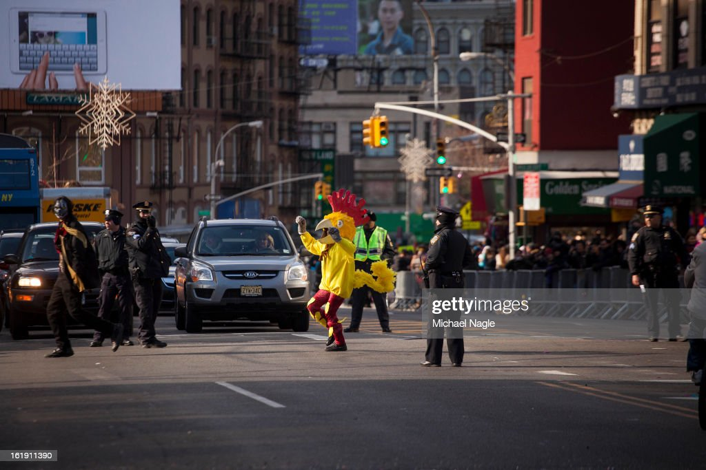 A person in a chicken costume crosses Canal Street during the 14th Annual Chinatown Lunar New Year Parade on February 17, 2013 in New York City. This year celebrates the Year of the Snake.