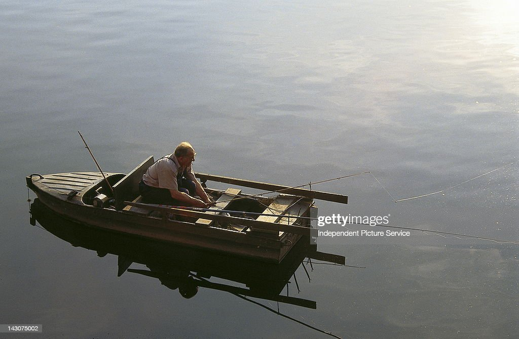 A person in a fishing boat on the Vltava River Prague Czech Republic