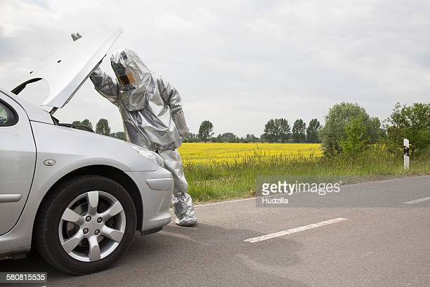 A person in a radiation protective suit looking under the hood of a car