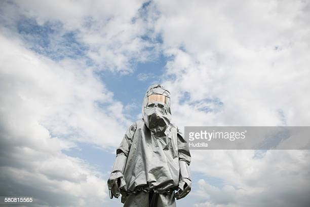 A person in a radiation protective suit standing against a cloudy sky