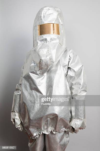 A person in a radioactive protection suit standing against a gray background