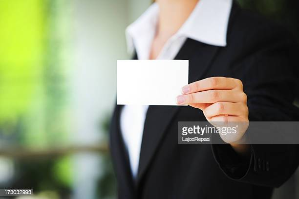 A person in a suit holding up a blank business card