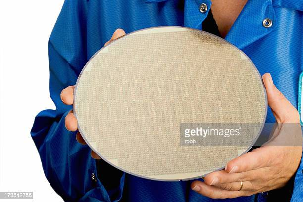 Person in blue holding a large silicone wafer
