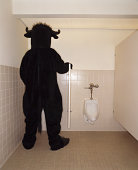 Person in bull costume using urinal, rear view