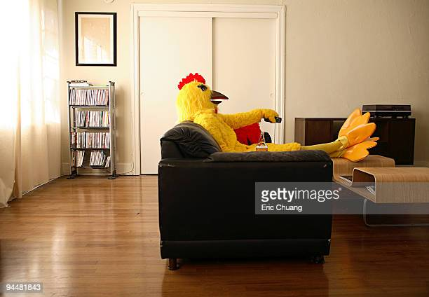 Person in chicken costume relaxing at home