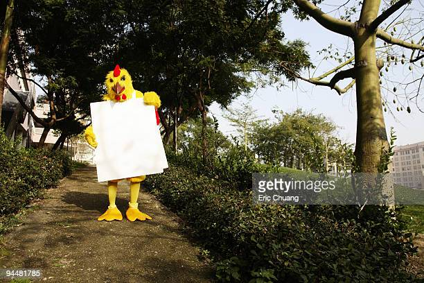 Person in chicken costume wearing signboard in forest