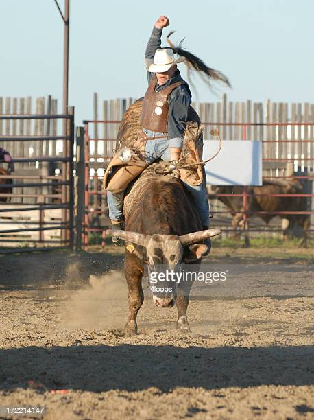 Person in cowboy hat riding bull in pen
