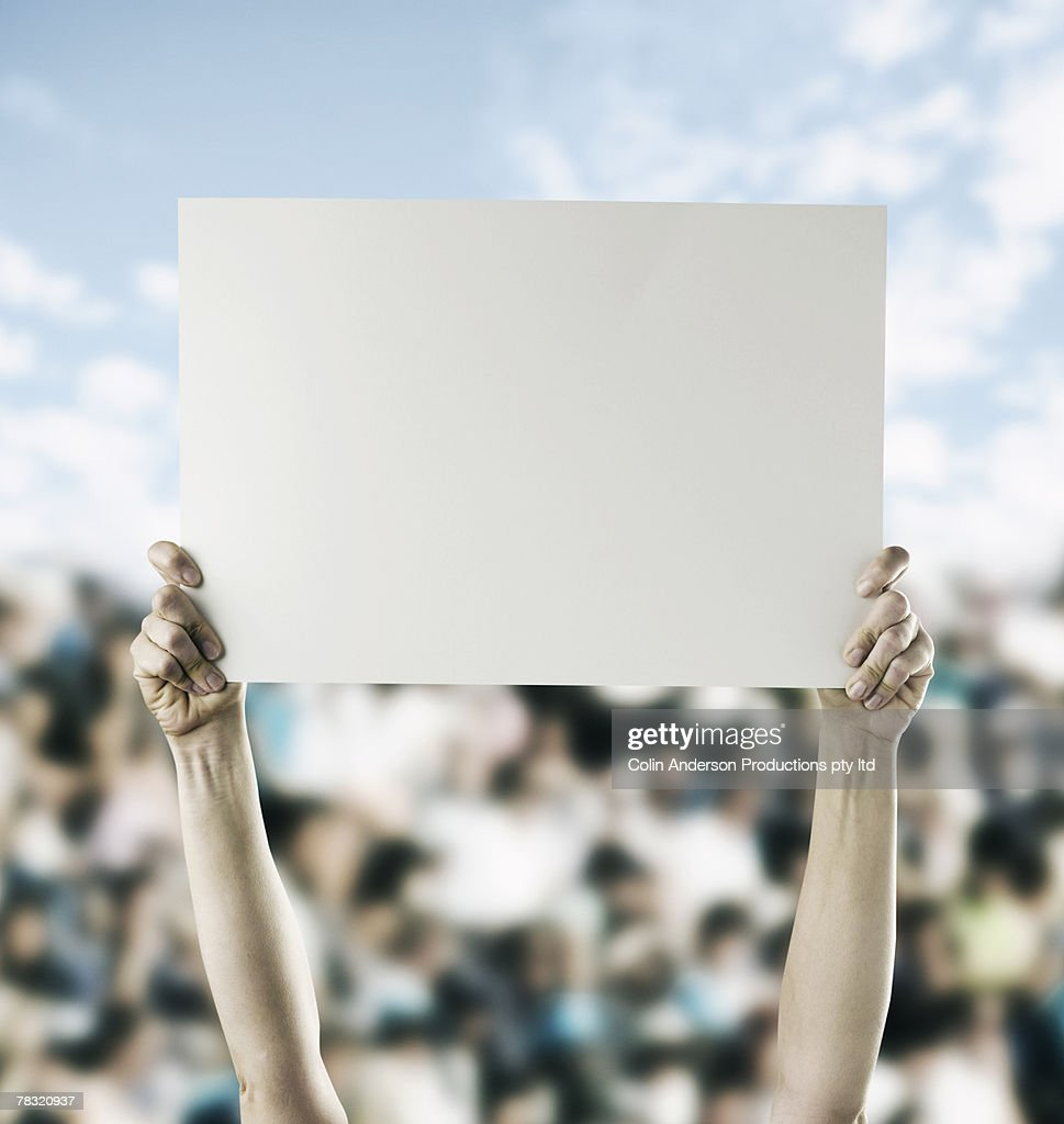 Person in crowd holding blank sign : Stock Photo