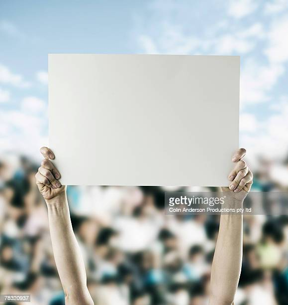 Person in crowd holding blank sign