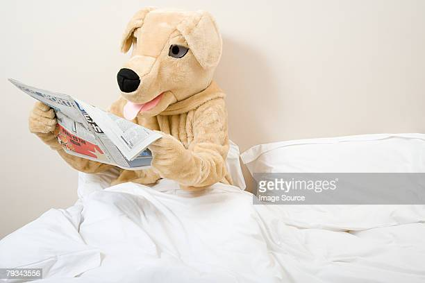 Person in dog costume reading newspaper