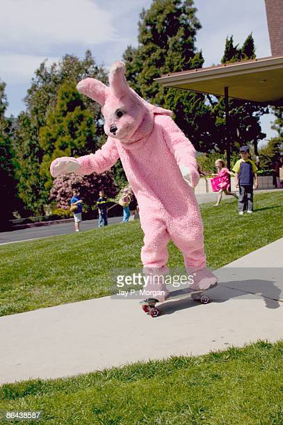 Person in Easter bunny costume riding skateboard