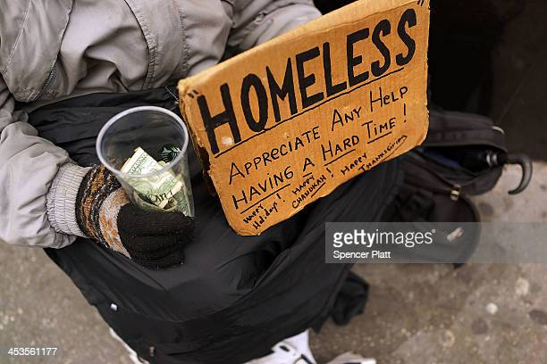 A person in economic difficulty holds a homemade sign asking for money along a Manhattan street on December 4 2013 in New York City According to a...