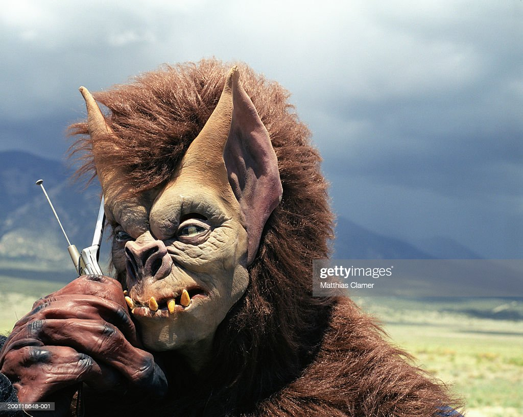 Person in monster costume using mobile phone, close up : Stock Photo