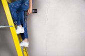 Person in overalls on ladder with drill