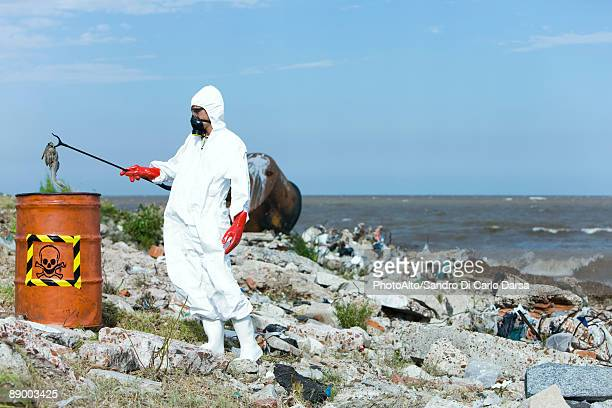 Person in protective suit placing dead fish in hazardous waste barrel