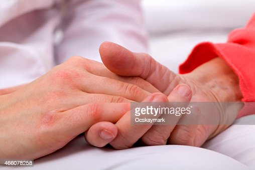 Person in red holding another person's hand over white : Stock Photo