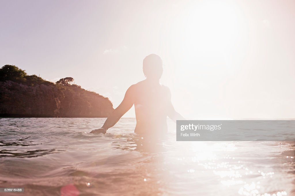 Person in sea at sunset : Stock Photo