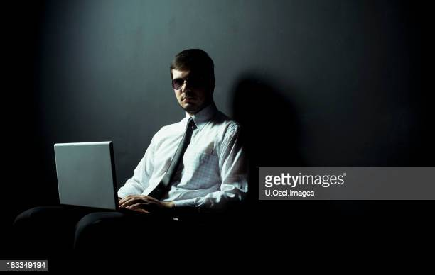 A person in sunglasses and a tie on a laptop in a dark room