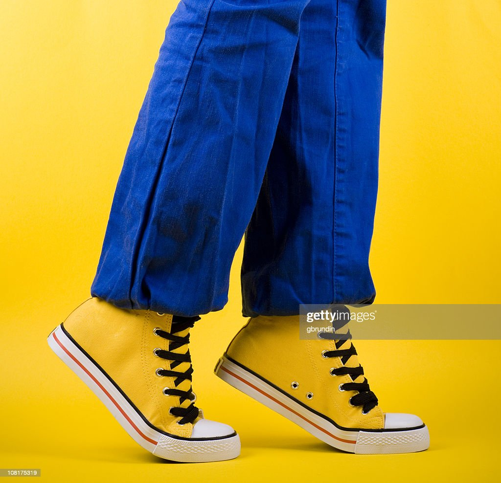 Person in Yellow Shoes Standing on Toes : Stock Photo