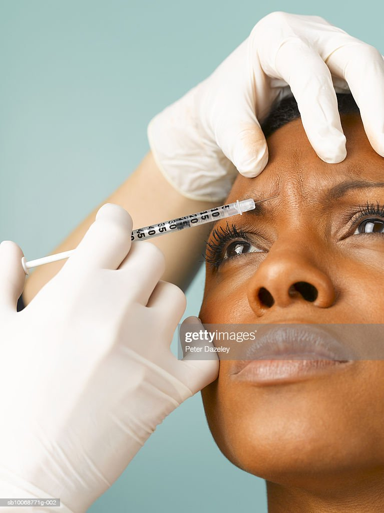 Person injecting botox into woman's forehead, close up, studio shot