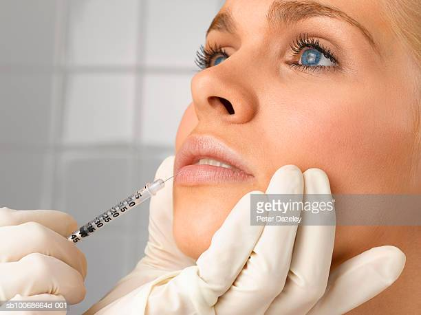 Person injecting young woman with small syringe, close up, studio shot