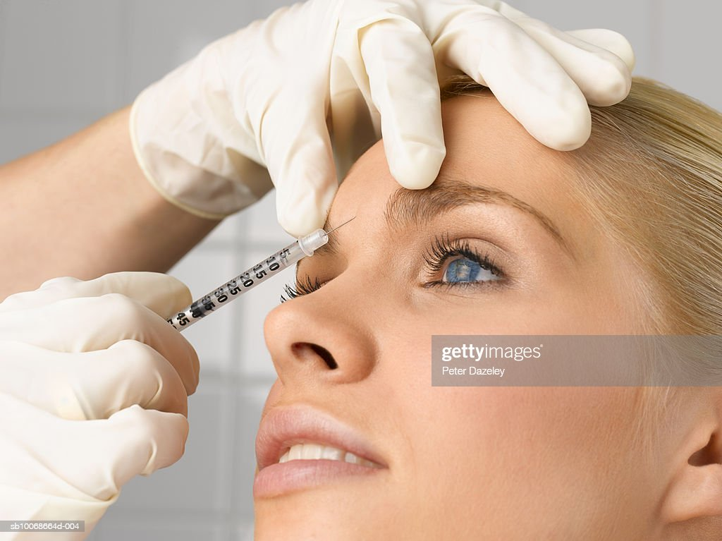 Person injecting young woman's forehead with small syringe, close up, side view, studio shot