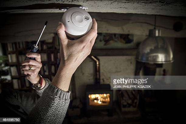 A person installs a smoke detector in a home in Lyon on February 26 2015 The Federation Francaise des Metiers de l'Incendie estimates in a projection...