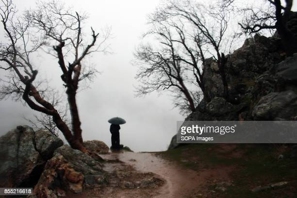 A person is pictured while holding an umbrella under the rain Every year in the Kurdish village of Uraman Takht in west Iran the locals celebrate the...