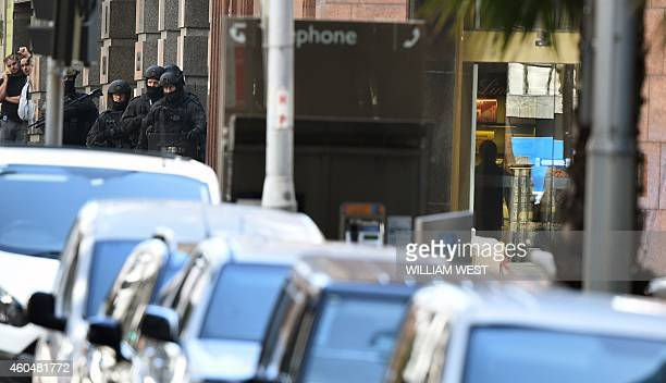 A person is seen in the door of the cafe as police stand ready nearby during a hostage siege in the central business district of Sydney on December...