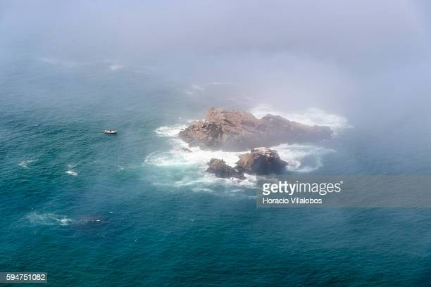 A person is seen through low clouds while climbing rocks on August 22 2016 in Cabo da Roca Sintra Portugal Cabo da Roca is a cape which forms the...