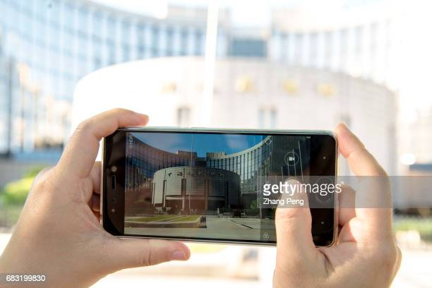 A person is taking picture of PBoC with a mobile phone To offer a longtime and sustainable financial support for the 'One belt One road' initiative...