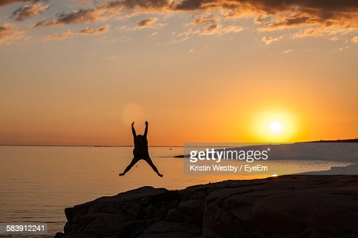 Person Jumping On Shore Against Sea During Sunset