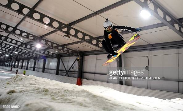 A person jumps with a snowboard at the Snowhall the only indoor ski run in France in Amneville eastern France on August 26 2016 as a heatwave strikes...