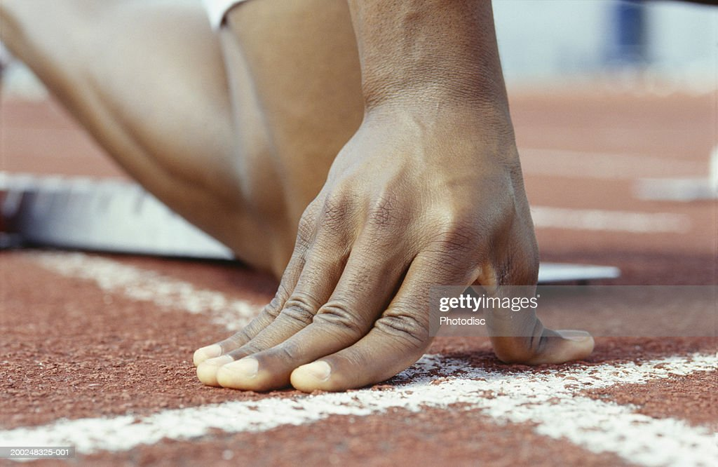 Person kneeling with hands on starting line, Close-up of hand