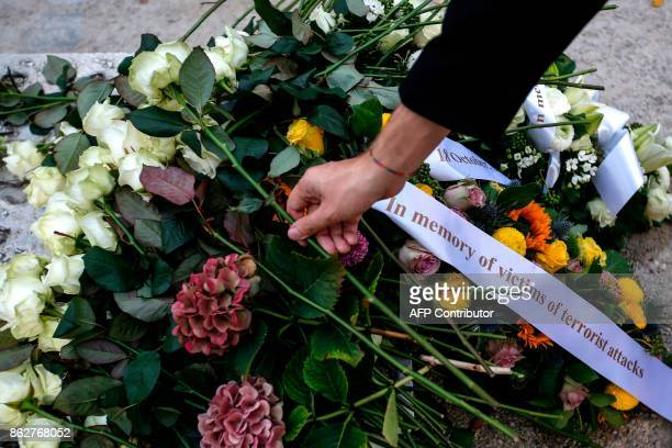 A person lays a white rose during a ceremony in support of victims of terrorism and emergency response services in Brussels on October 18 2017 The...