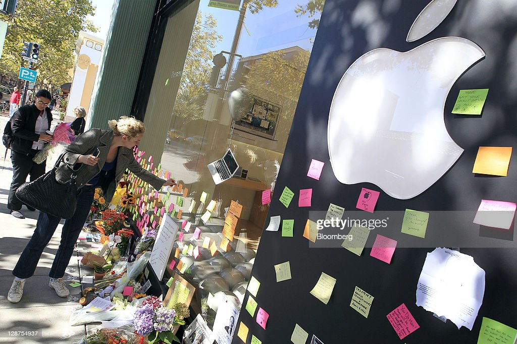 Cacilla Mueller, of Germany, leaves a post-it note at a memorial for Steve Jobs, co-founder and former chief executive officer of Apple Inc., outside an Apple store in Palo Alto, California, U.S., on Friday, Oct. 7, 2011. Jobs, who built the world's most valuable technology company by creating devices that changed how people use electronics and revolutionized the computer, music and mobile-phone industries, died on Oct. 5. He was 56. Photographer: Tony Avelar/Bloomberg via Getty Images