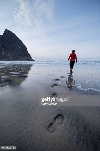Person leaves footpints in sand at scenic Kvalvika beach, Moskenesoy, Lofoten Islands, Norway